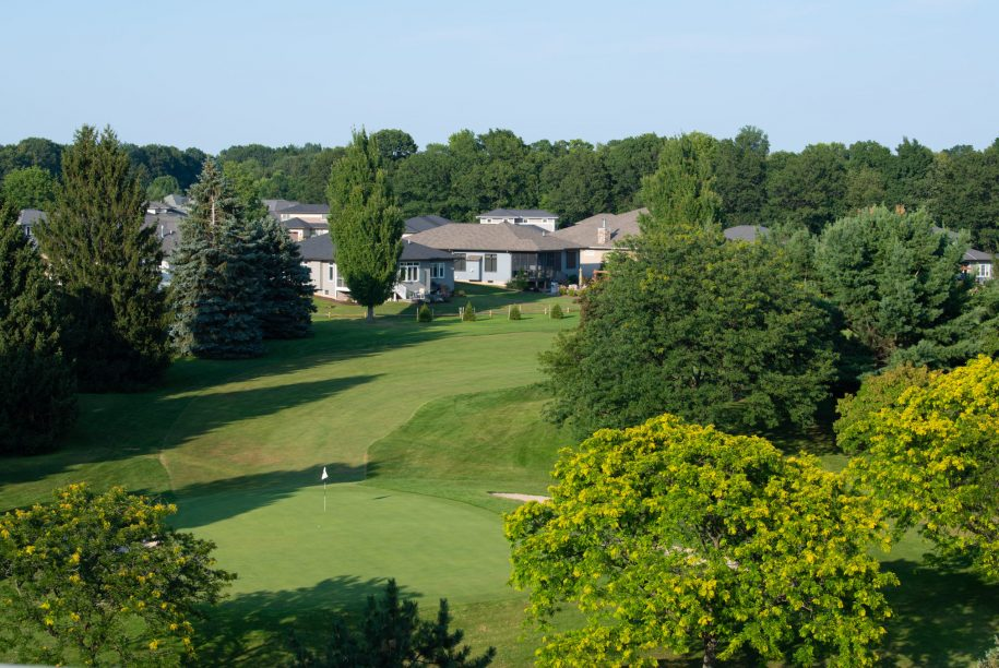 Ariel shot of fairway and greens overlooking nearby homes